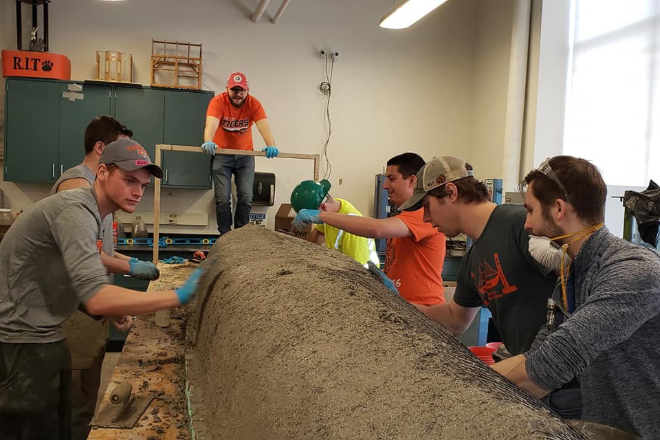 Students put concrete on wire frame of canoe body.