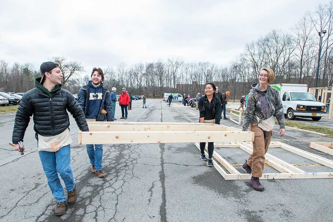 Four students walk through parking lot with wall frame.