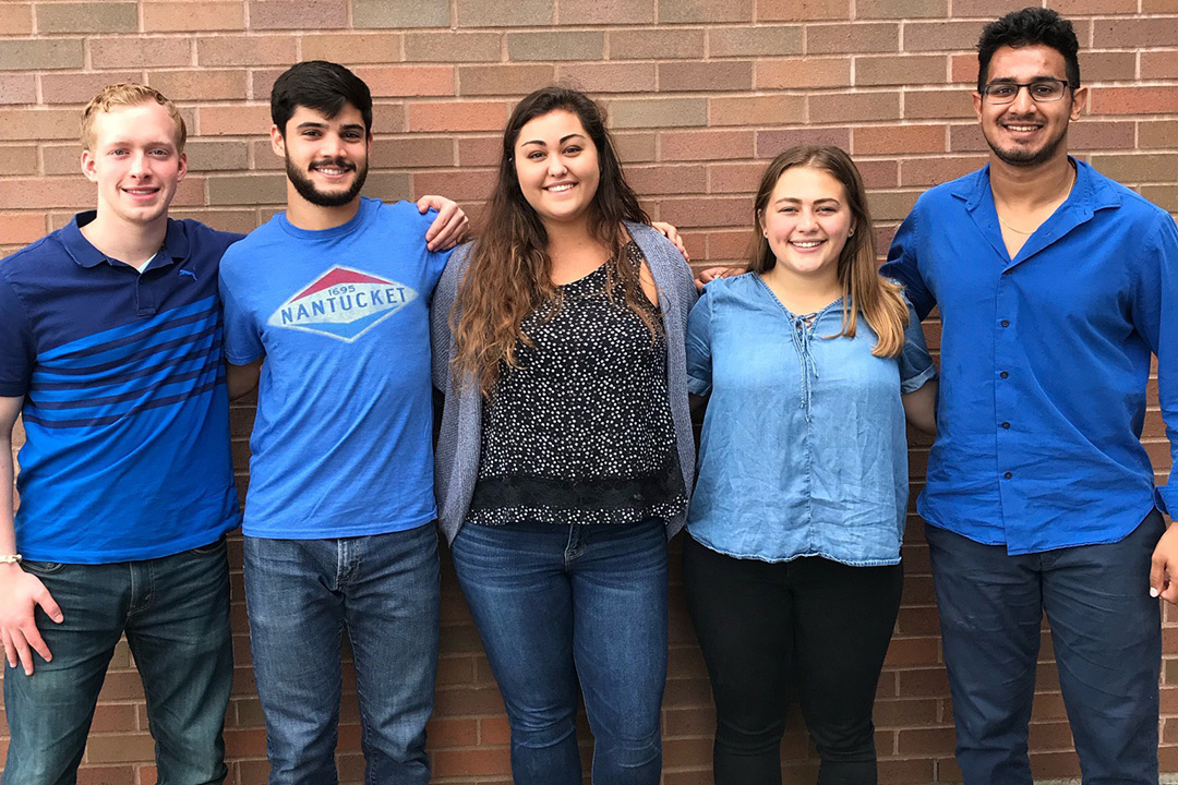 Group of five students stands against a brick wall.
