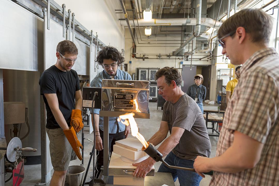 A group of artists stand around a molten glass 3D printer.