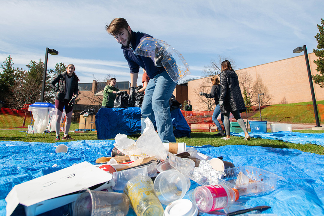 Student sorts pile of recyclables.