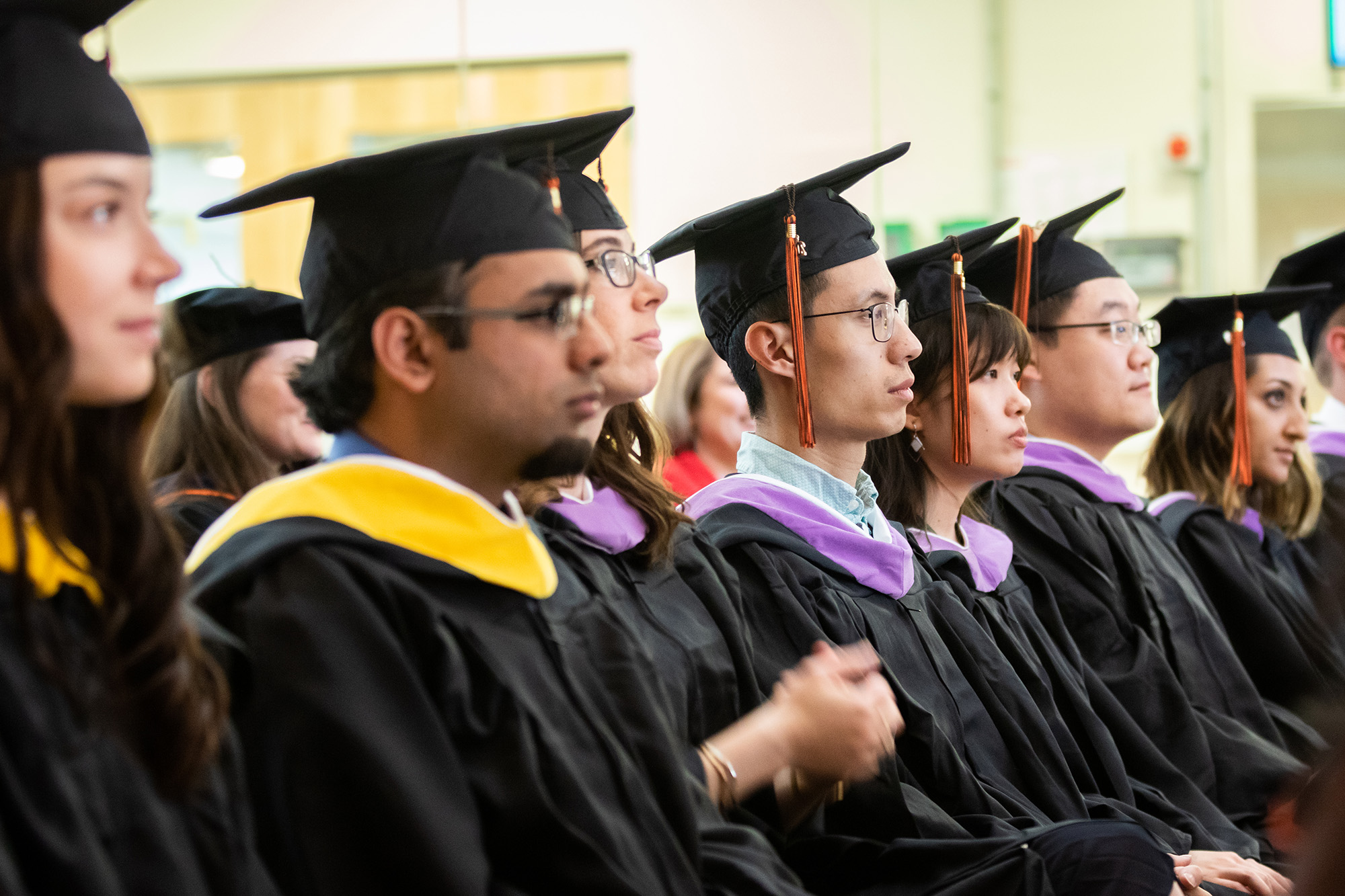 Students sitting, wearing graduation caps and gowns.