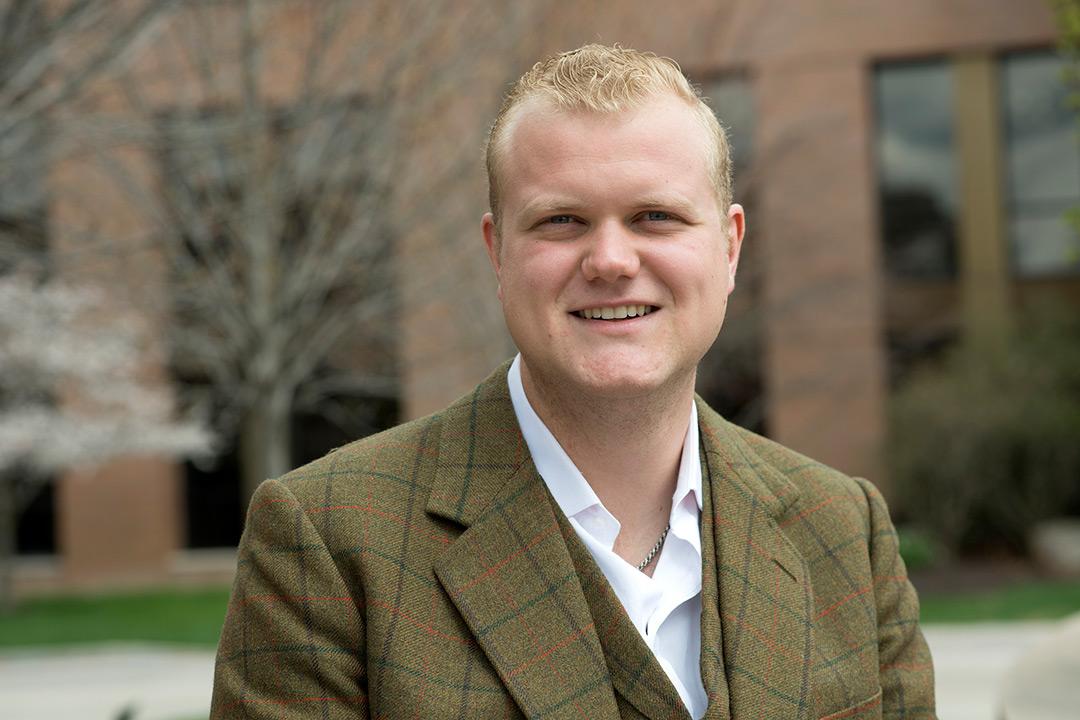 Man in plaid tweed jacket poses outside.