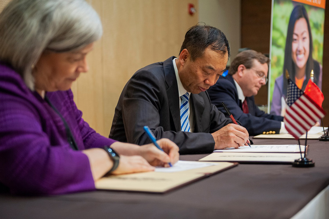 Three people sit at table signing papers.
