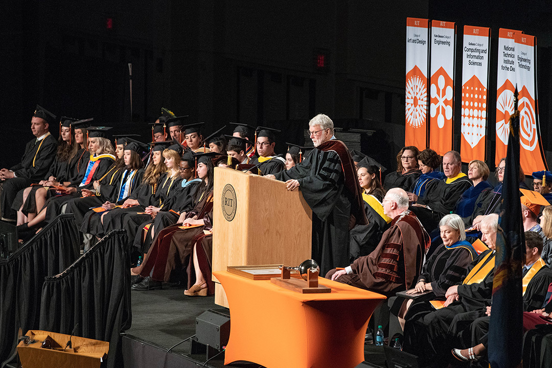 Man in commencement regalia speaks at podium on stage.