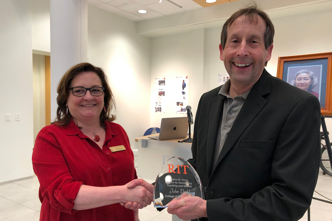 Man and woman pose with glass award.