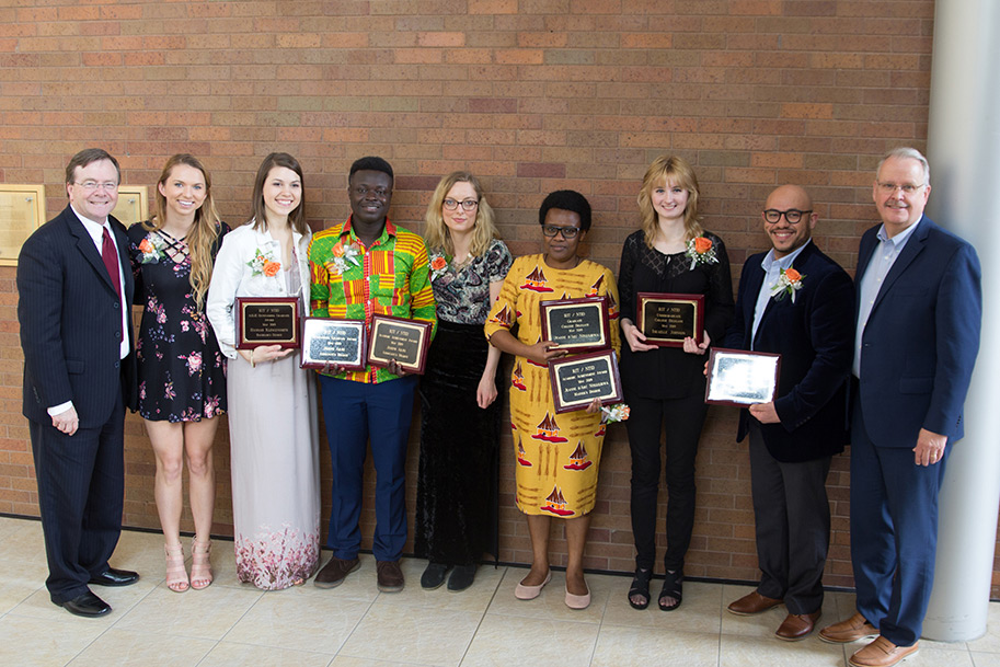 Group shot of several students holding awards.