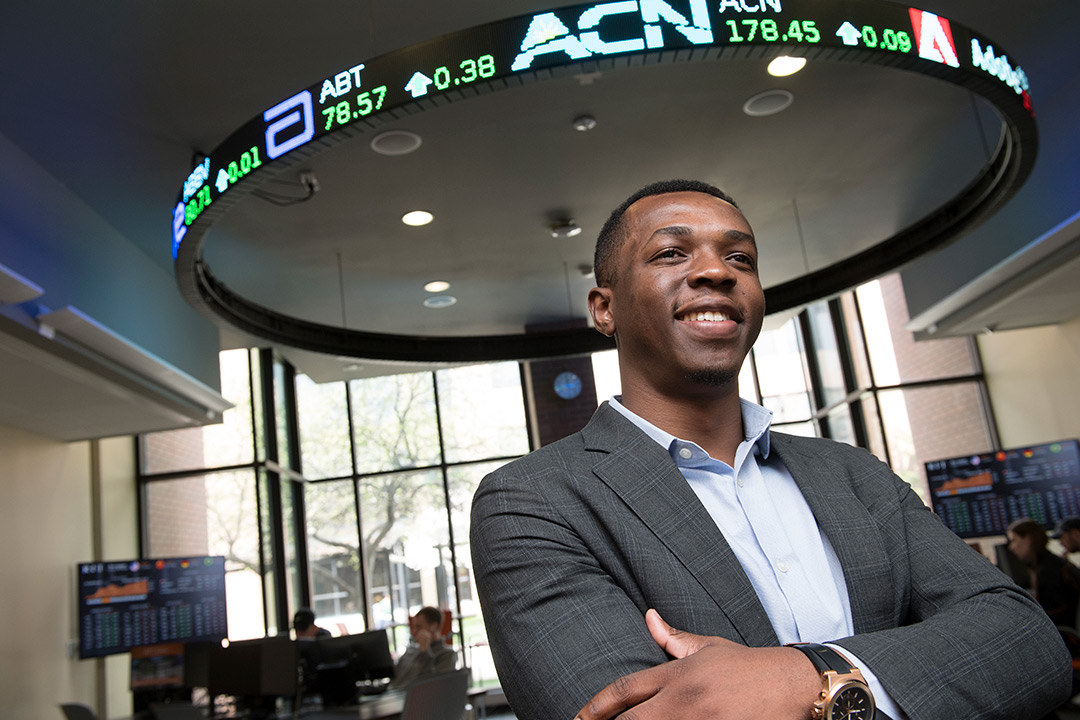 Student poses below stock ticker sign.