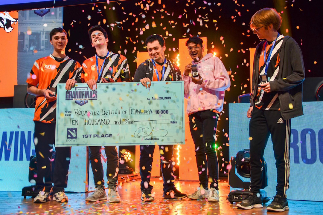 Five team members hold giant check on stage as confetti drops.