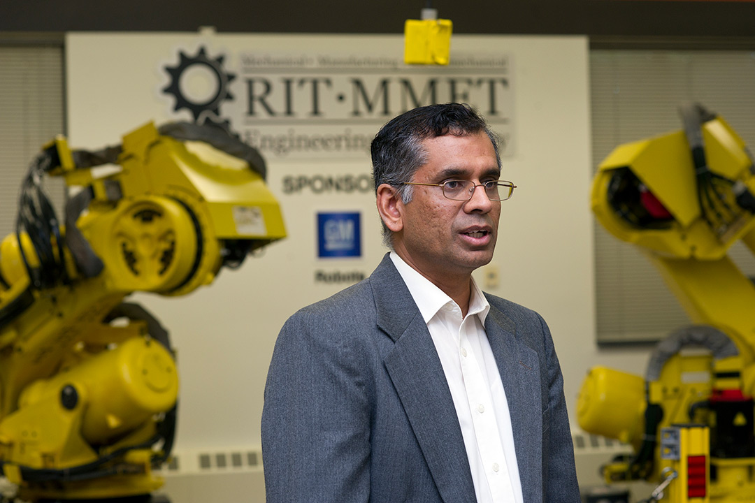 Man stands in front of yellow industrial robots.