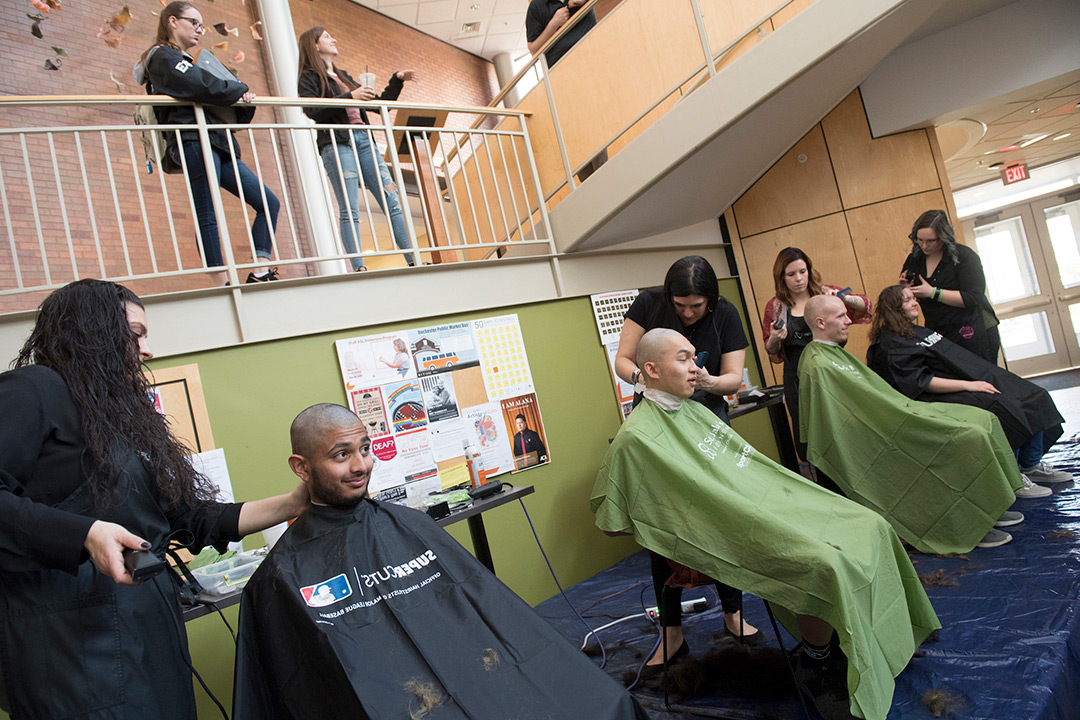 Four participants sit in barber chairs and have their heads shaved.