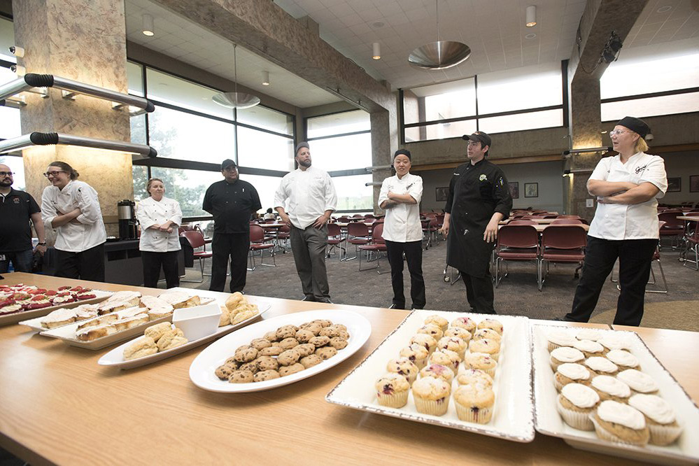 Libe of chefs stands behind table with plates of desserts.