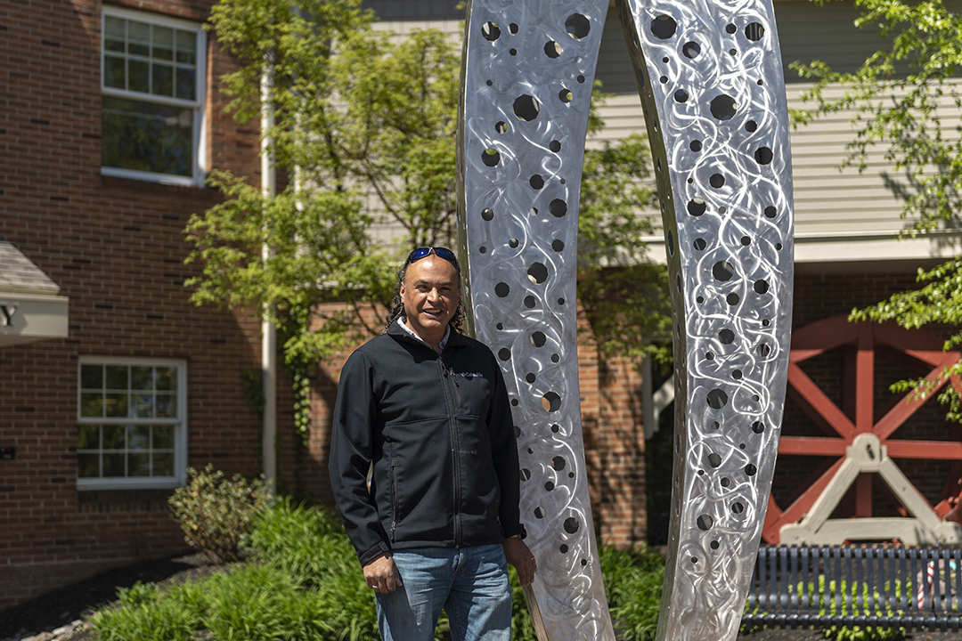 "'Carlos Caballero-Perez stands beside his newest sculpture, ""Connection""'"