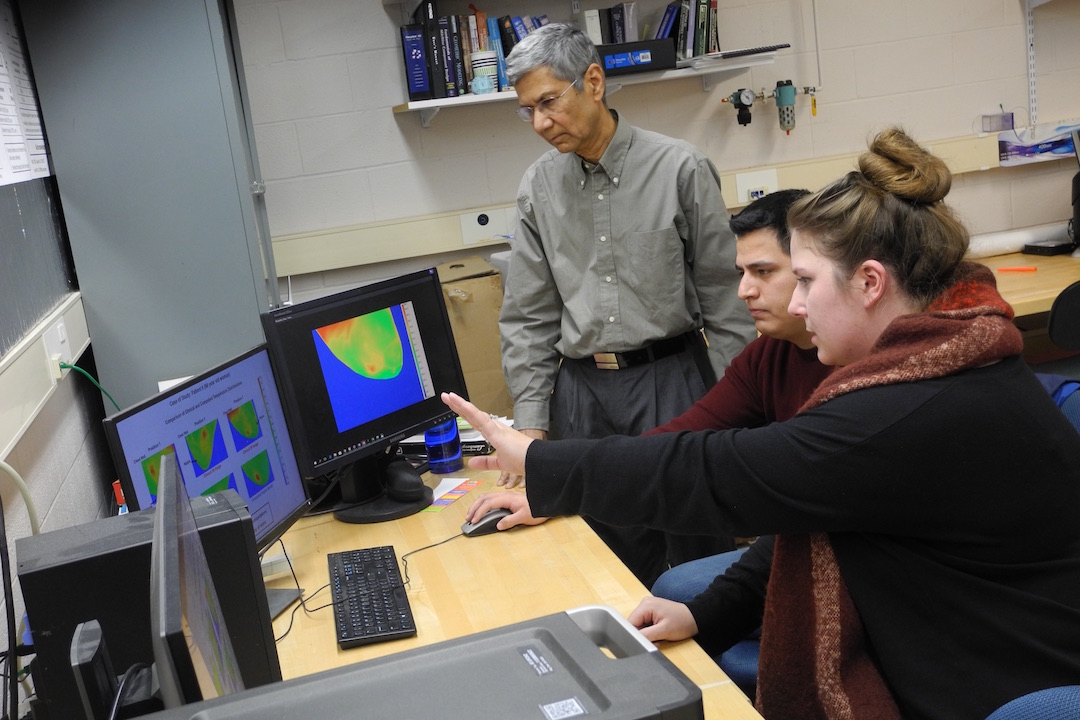 Two students and a professor work on a computer with infrared imaging of cancerous tumors.