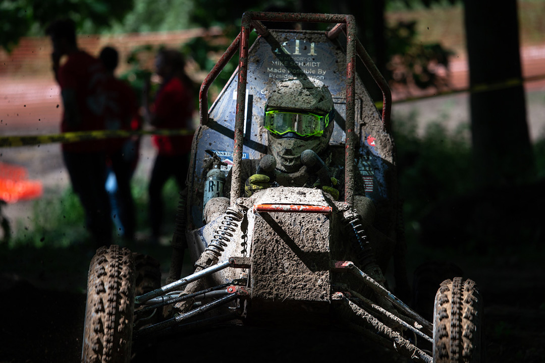 Head-on view of baja car and driver covered in mud.