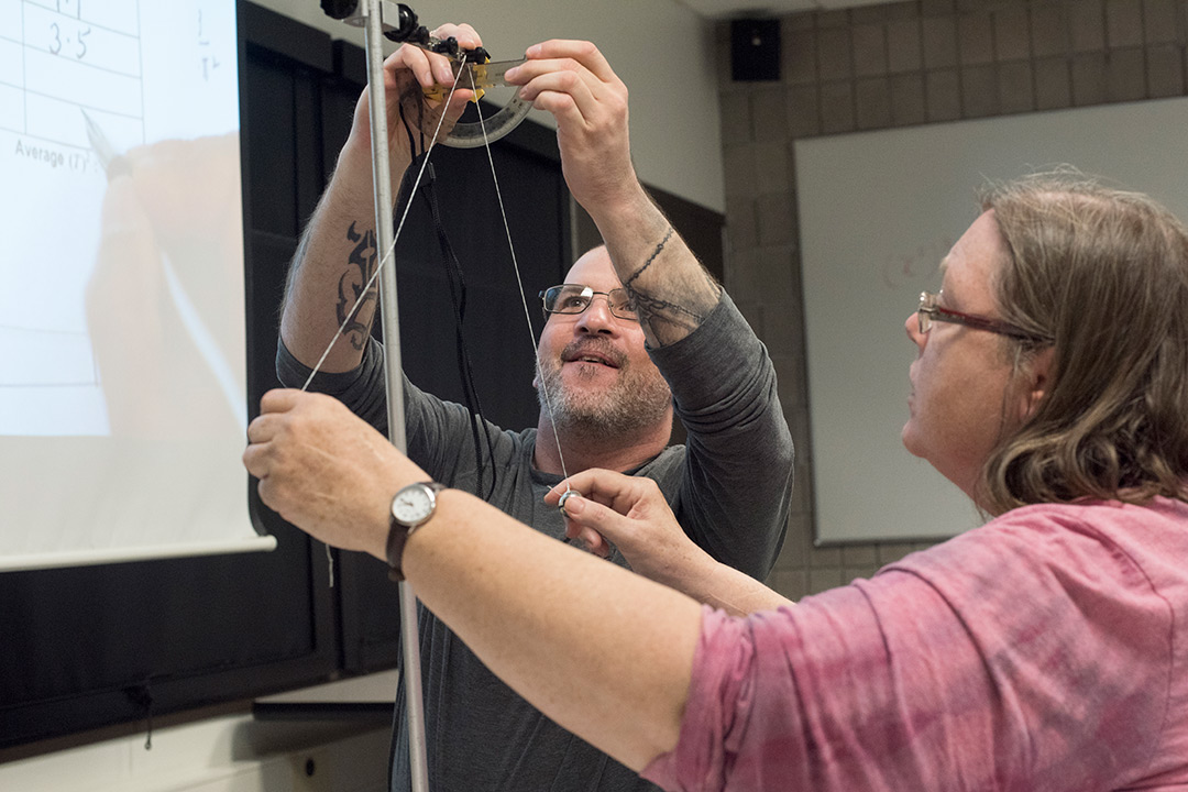 'Adult students conduct experiment with protractor.'