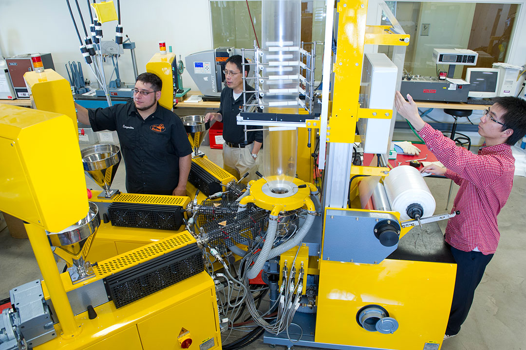 Students work with large, yellow machinery.