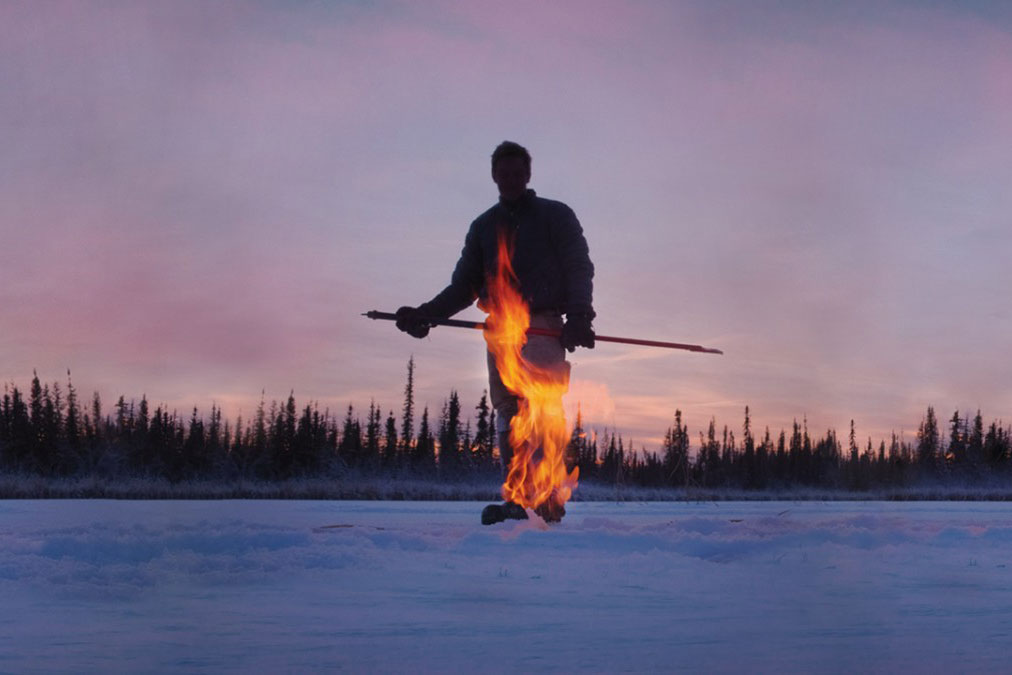 Person walks across snow as flame shoots up from pipe in the snow.