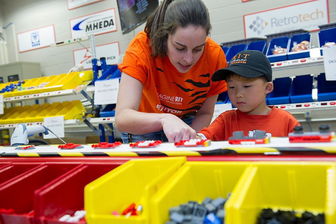 College student shows child an assembly line with Lego pieces.