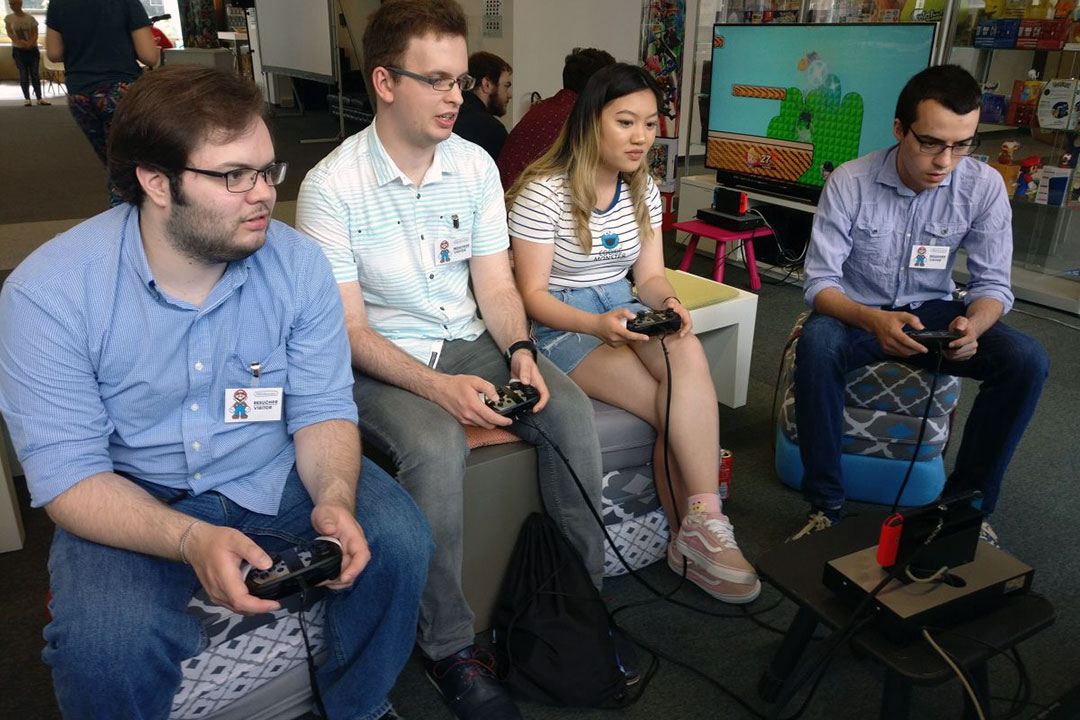Four students play Nintendo.