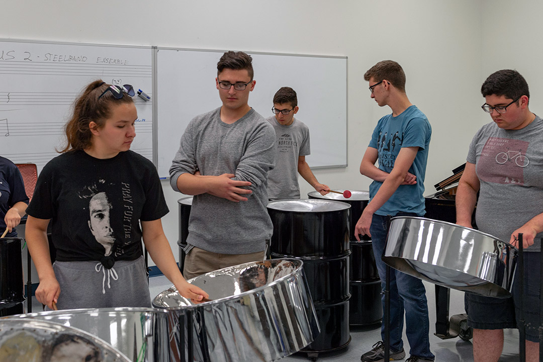 'Students play steel drums.'