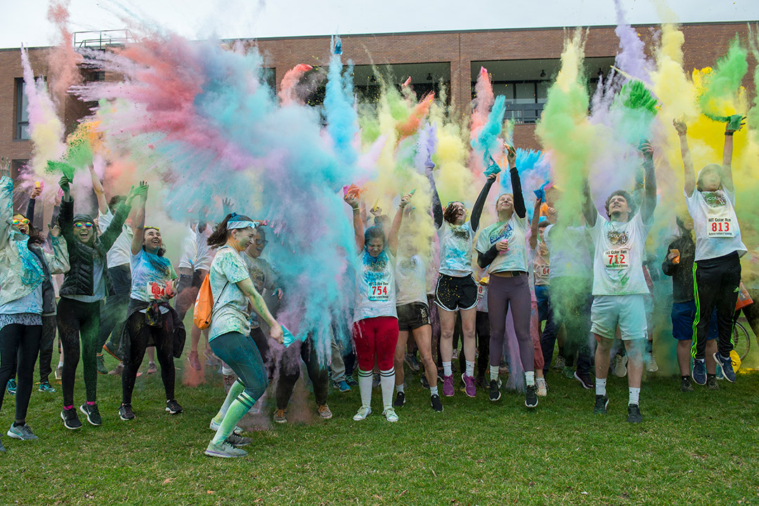 'Student throw colored powder up into the air.'