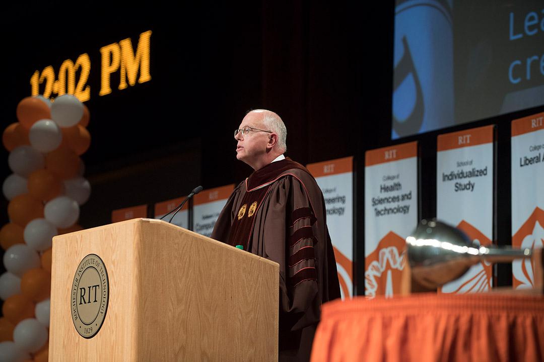 'President Munson speaks at podium.'