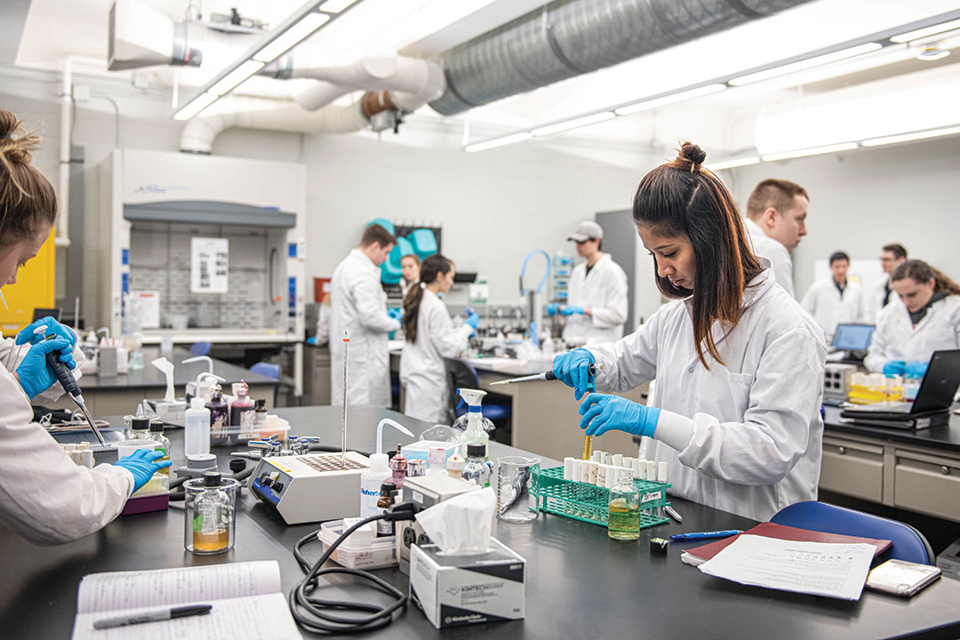 'Student in lab coat works with pipette.'