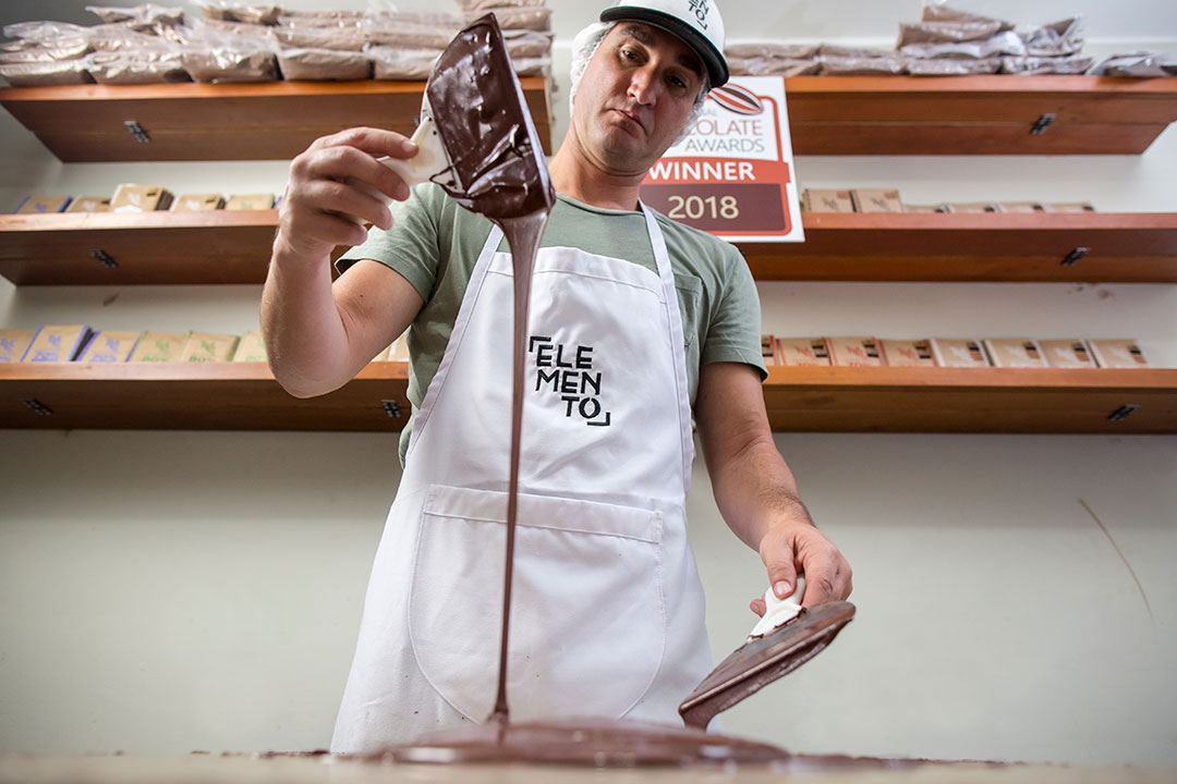 'Chocolate-maker drips chocolate off of spatula.'