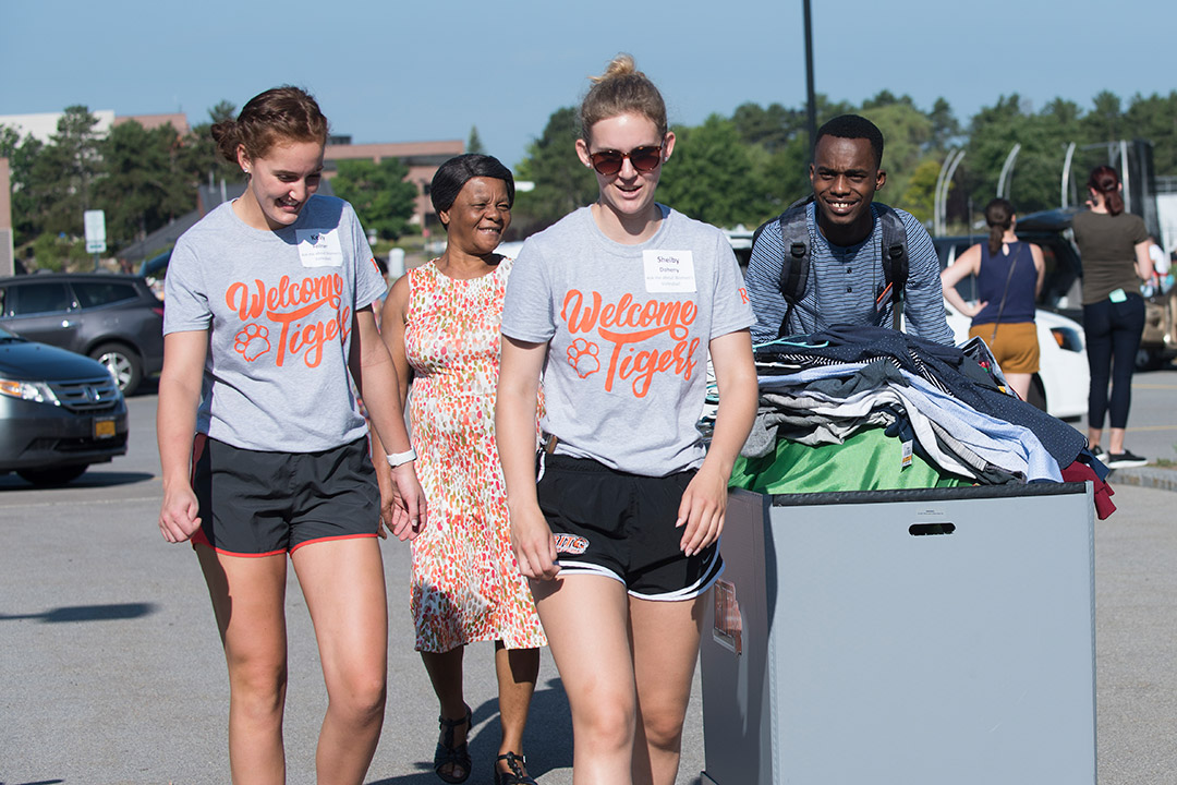 'Students and parents bring items in cart for move-in day.'