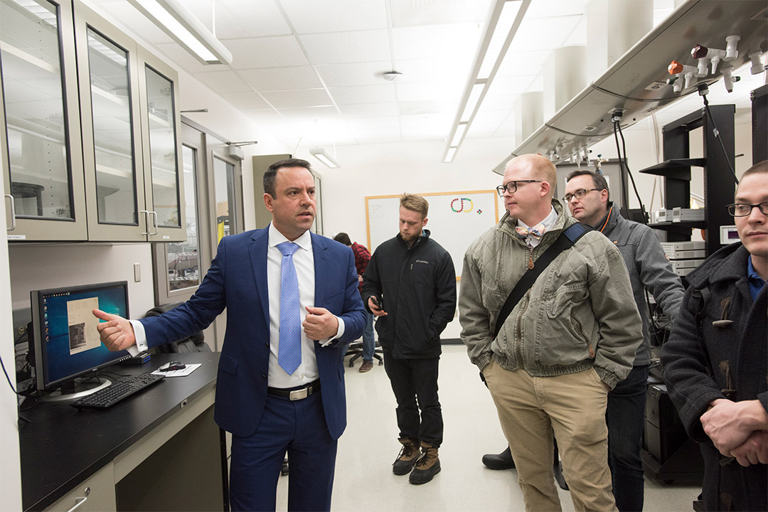 Man in suit leads tour of lab facility.