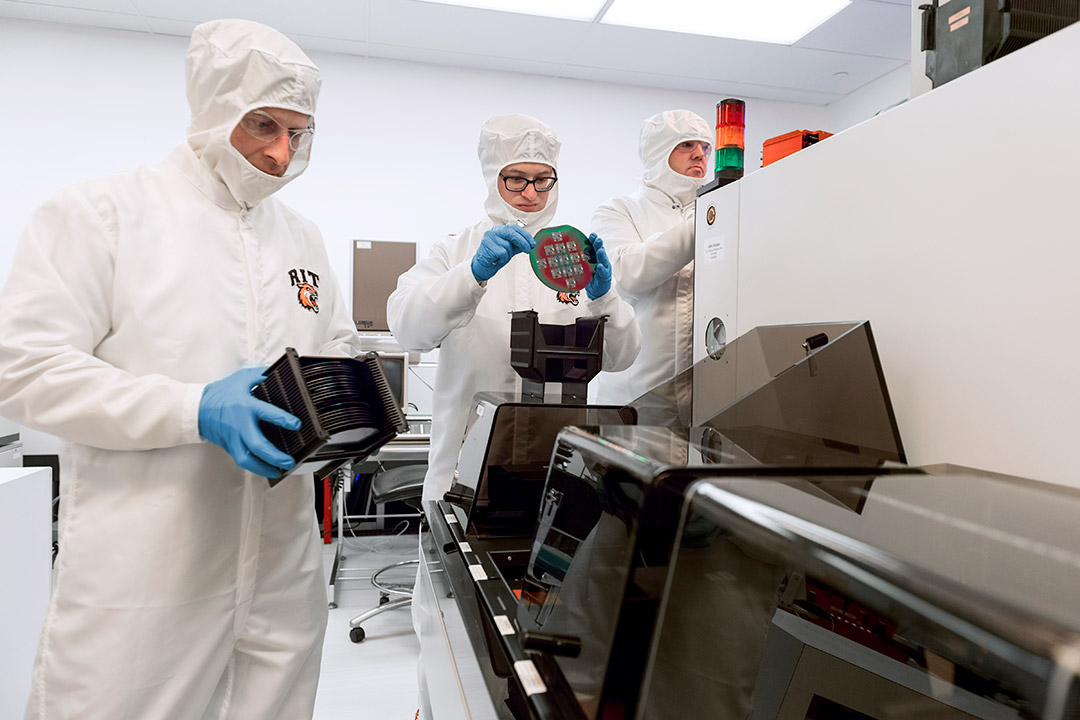 'Researchers wearing white cleanroom suits handle circuits.'