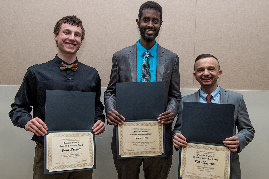 'Jacob Schwall, Bakar Ali and Peter Bilzerian stand holding awards.'