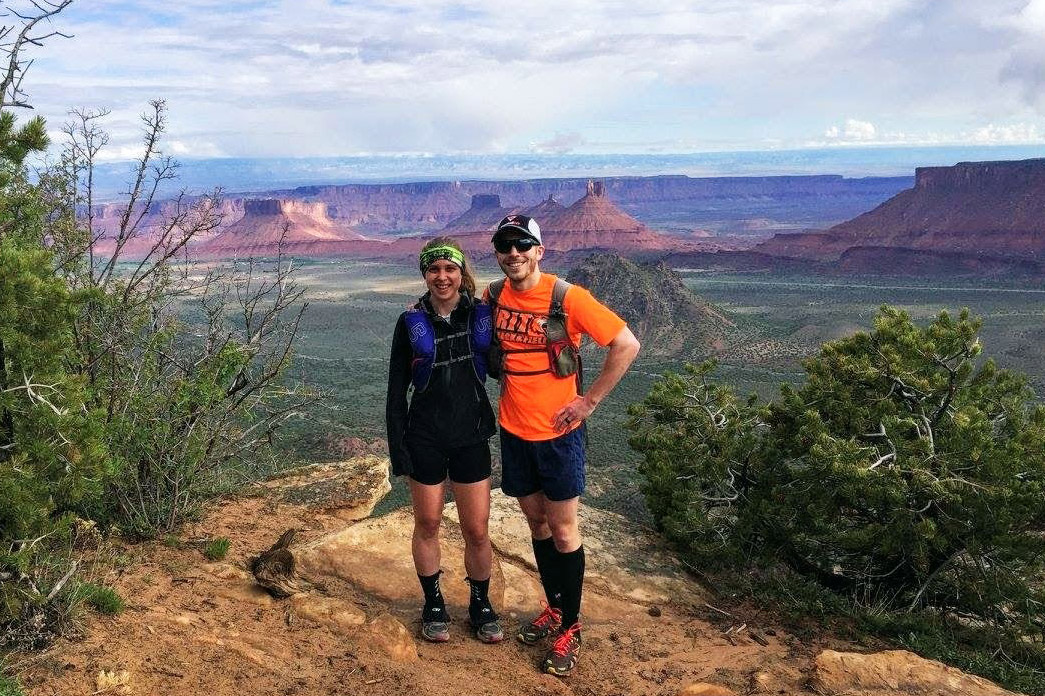 Couple in hiking gear stands on ledge with canyon in background.