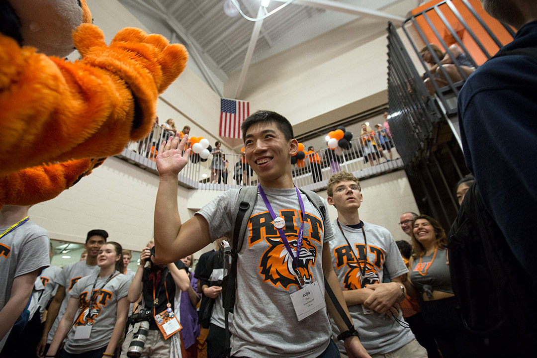 'New student high-fives Tiger mascot.'