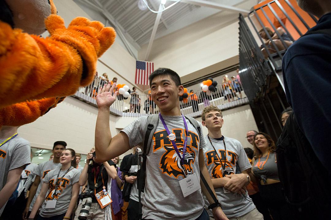 New student high-fives Tiger mascot.