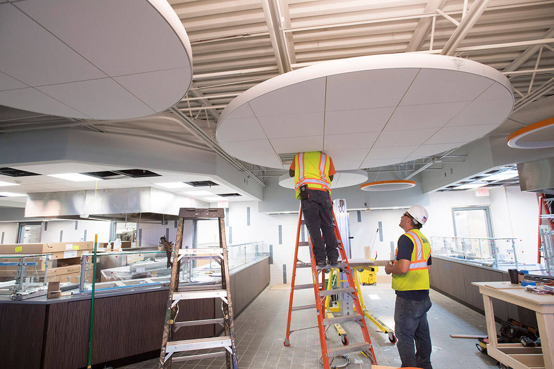 'Contractors stand on ladder to work on ceiling in dining hall.'