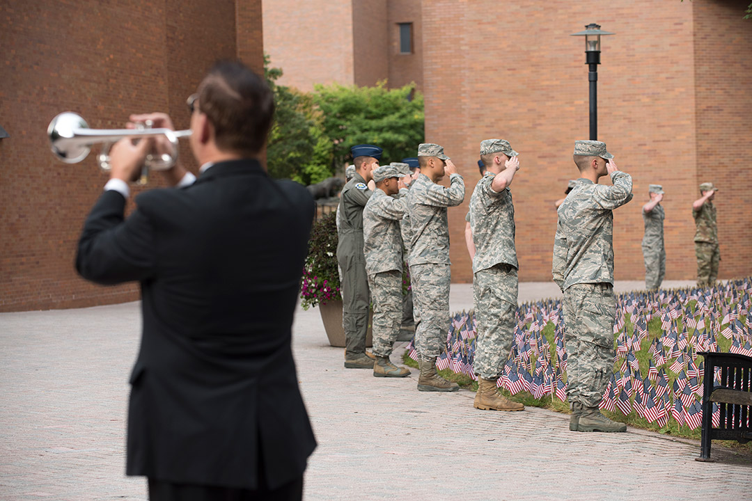 'Man plays Taps while ROTC members salute field of American flags.'