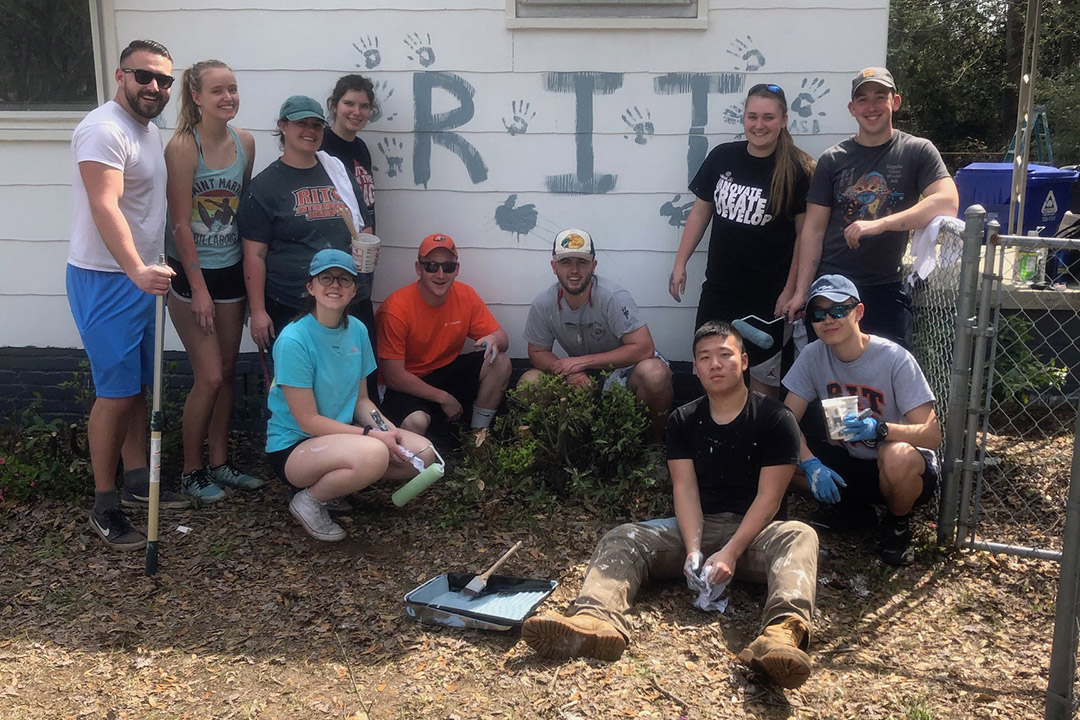 'Group of students outside of house painted with the letters RIT and handprints.'