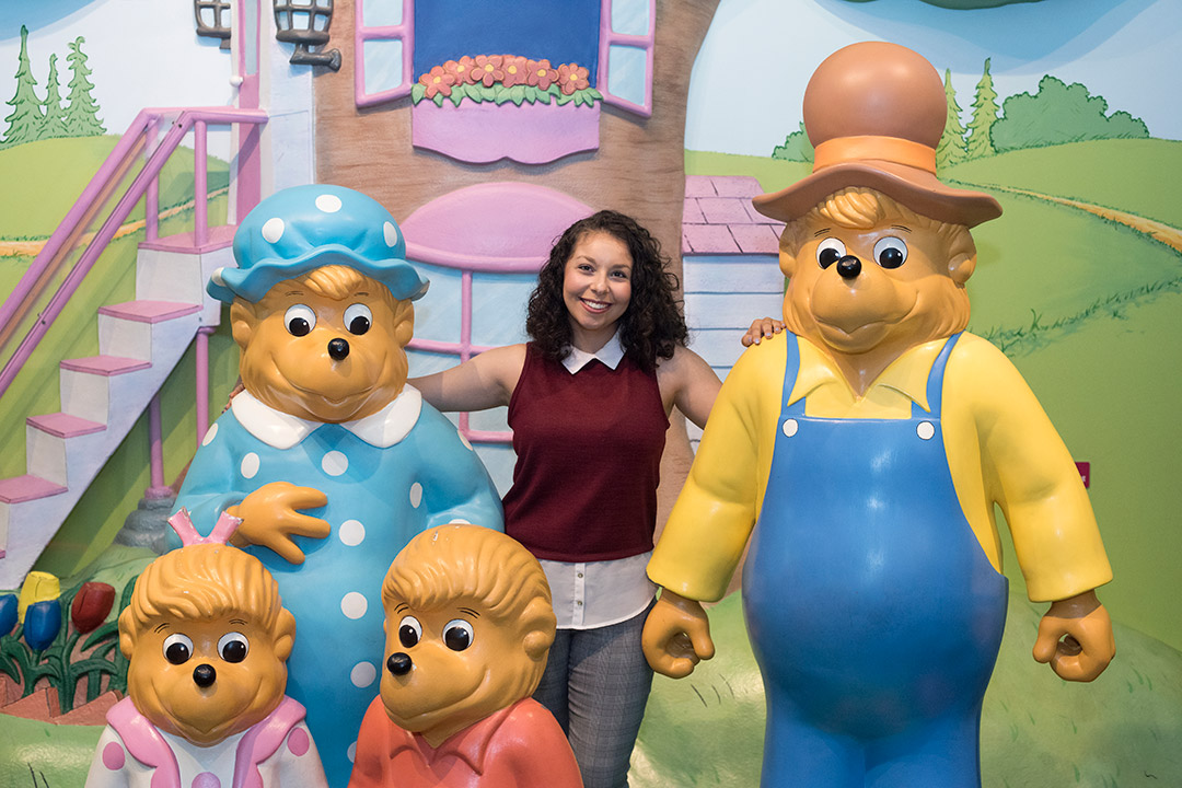 Student stands with life-like statues of the Berenstain Bears.
