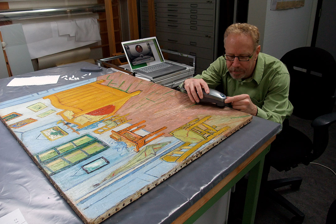 'Scientist measures color on painting.'
