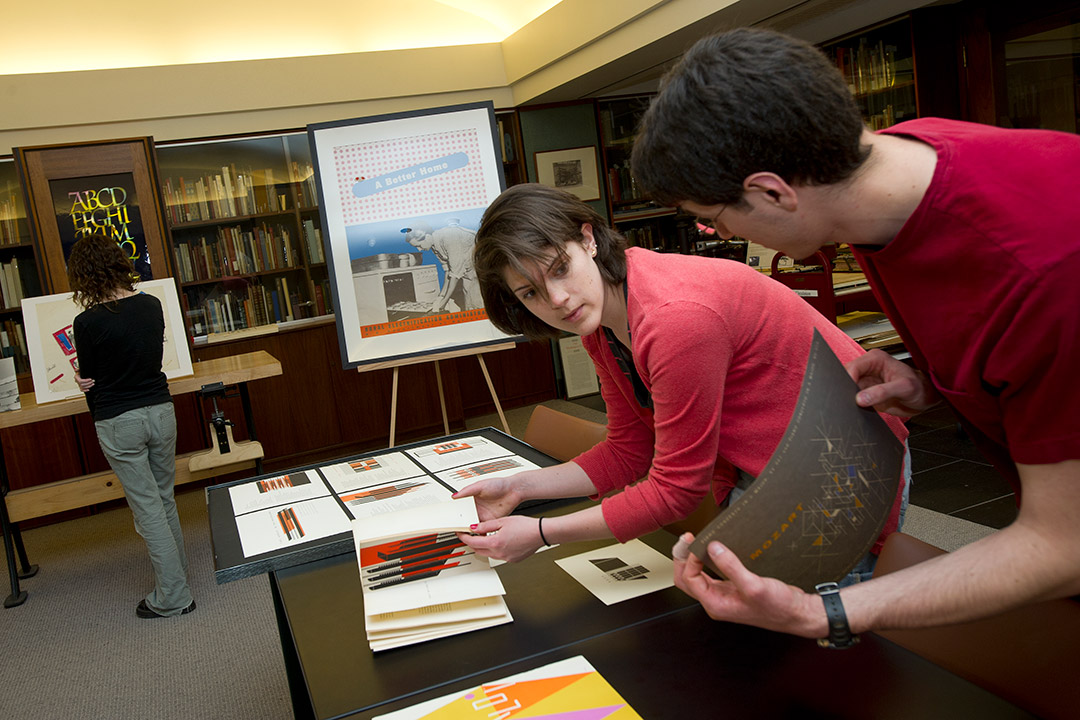 Students look at materials in library.