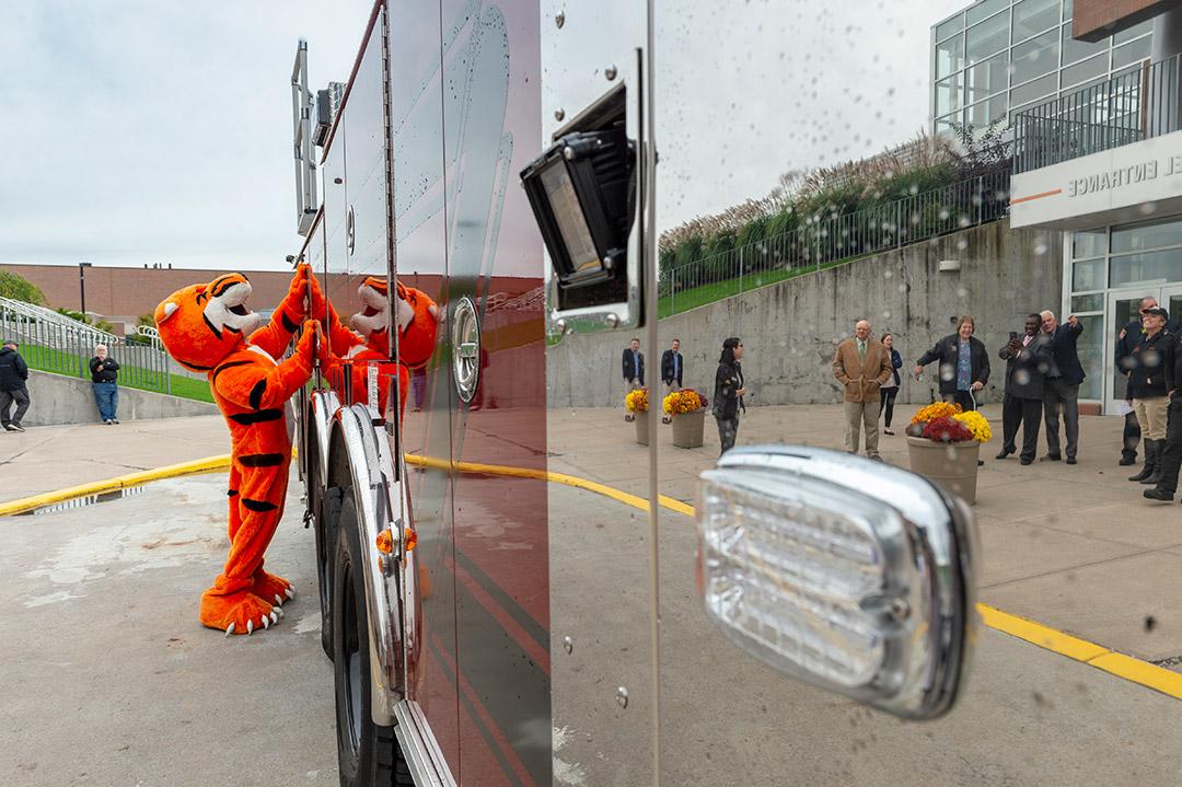 'Tiger mascot looks at firetruck'