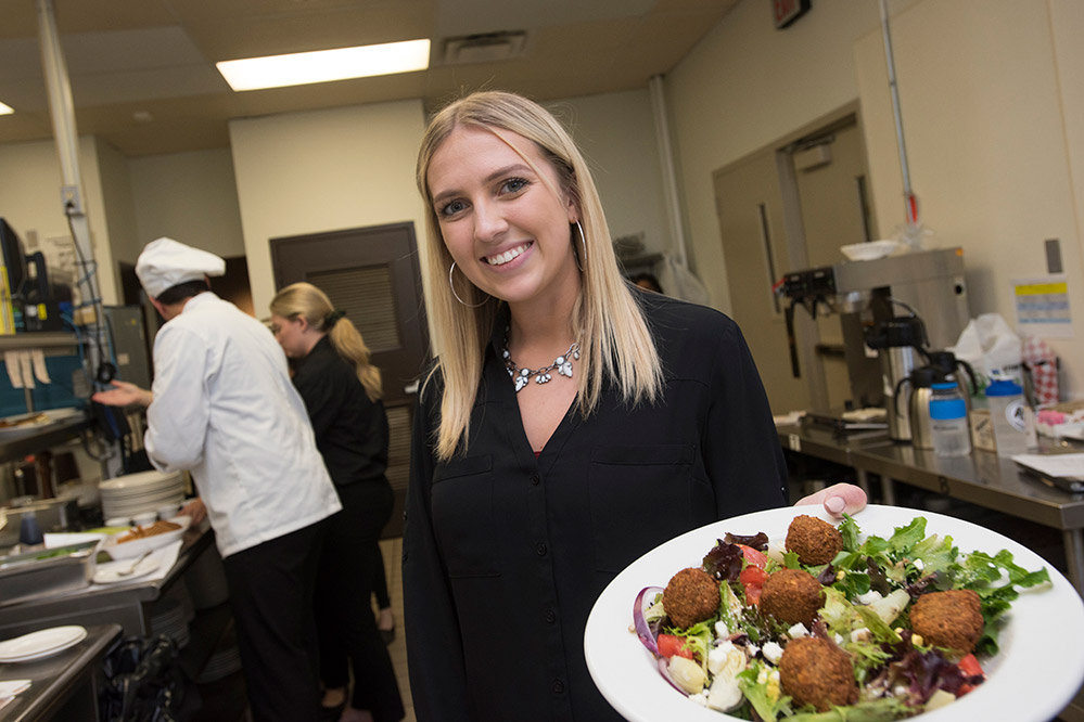 'Student stands in restaurant kitchen holding plate of salad.'