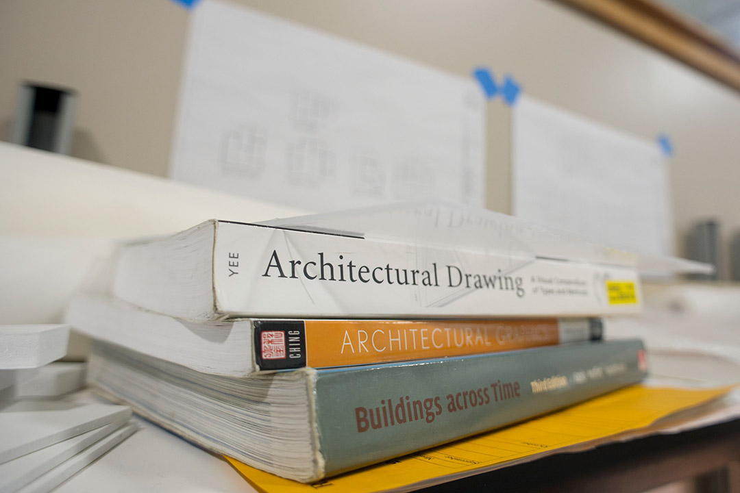'Three architecture books stacked on top of each other on table.'