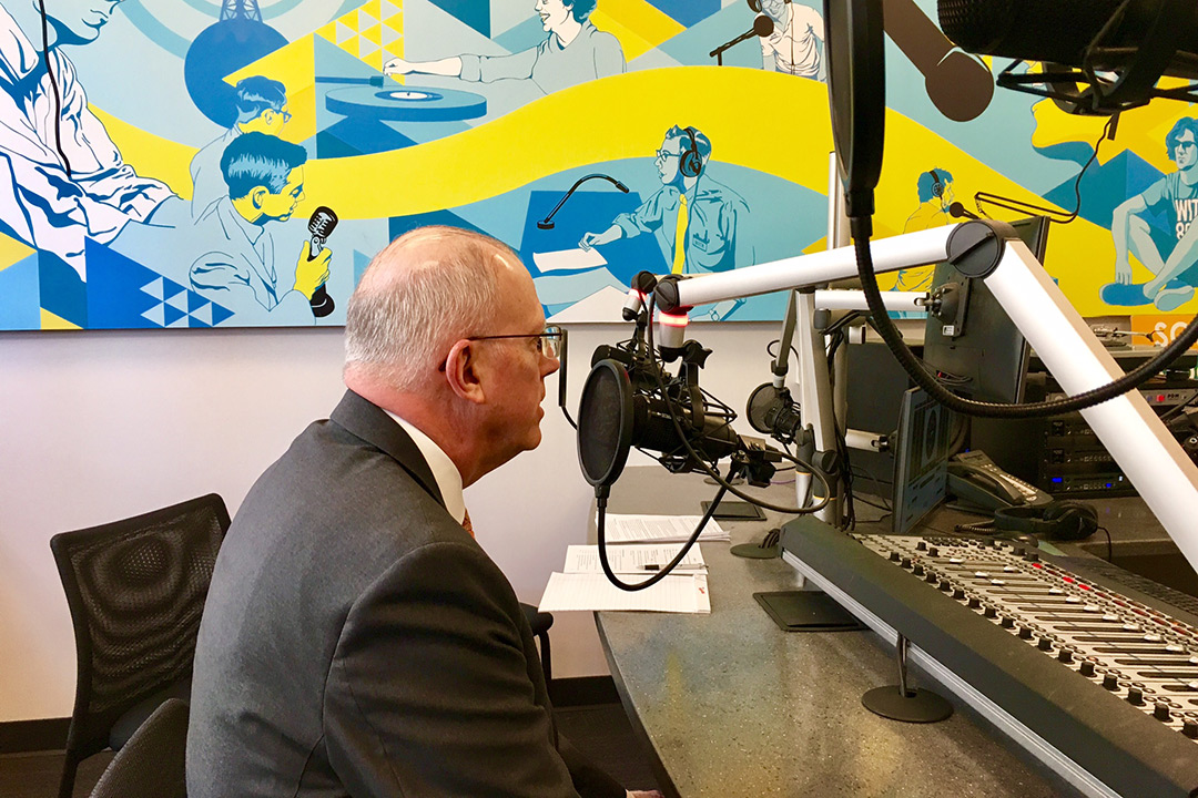 'Dave Munson speaks into microphone in radio station studio.'