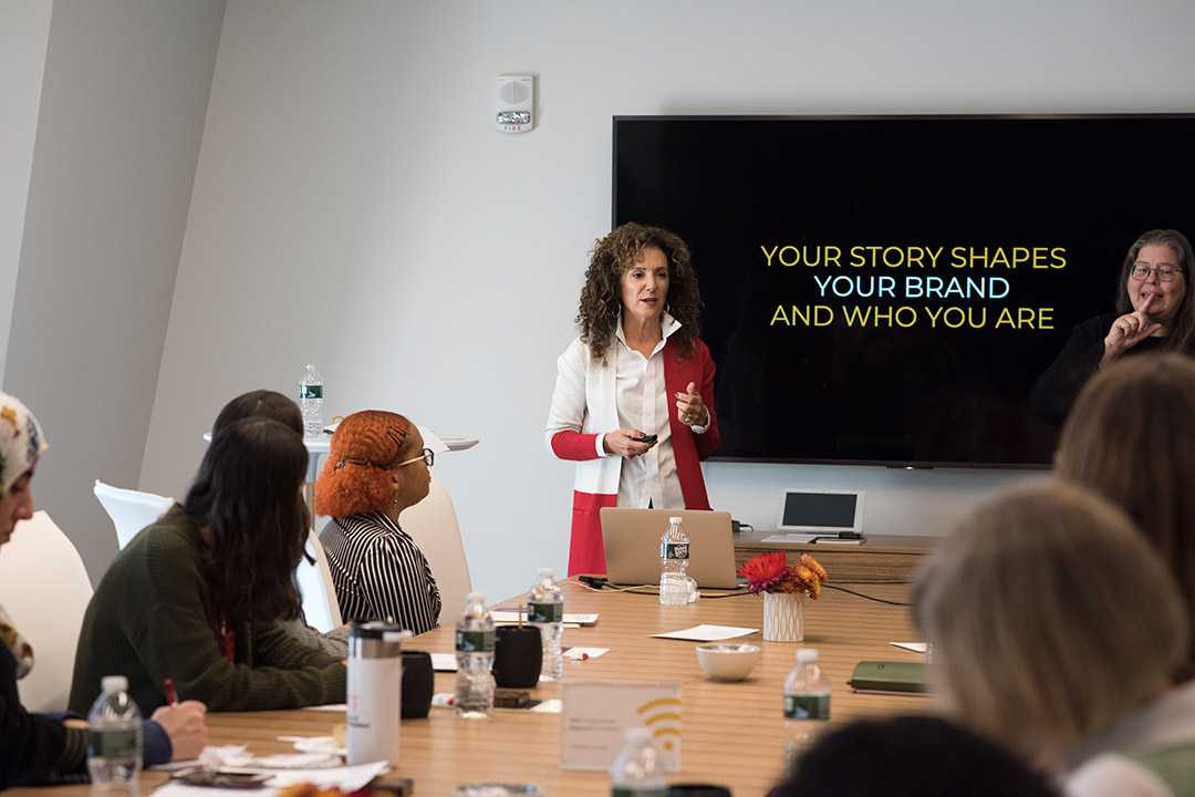 "Sharon Napier stands in front of TV screen to present ""Your story shapes your brand and who you are."""