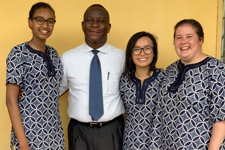 'Students wearing traditional Nigerian dress stand with professor.'