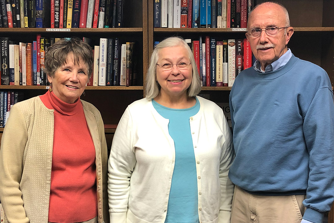 Three Osher students stand in front of bookcase.
