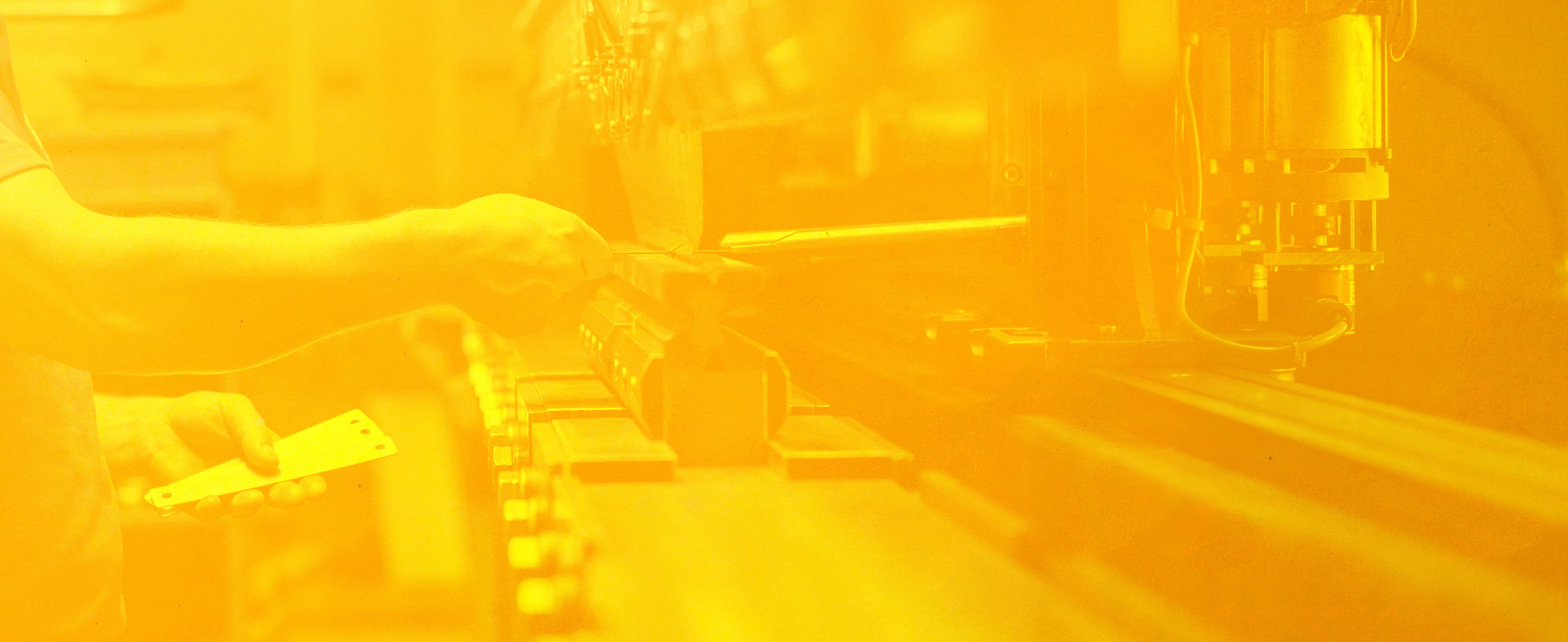A closeup of a worker's hands using a machine in a factory with orange overlay